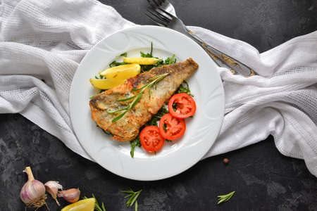 Fried fish fillet with tomatoes, lemon and rosemary. White plate. Dark background. White linen napkin. Top view