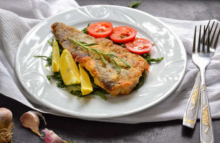 Fried fish fillet with tomatoes, lemon and rosemary. White plate. Dark background. White linen napkin.