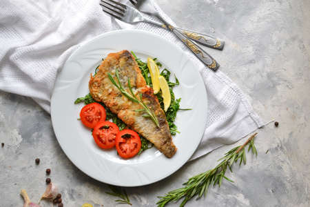 Fried fish fillet with tomatoes, lemon and rosemary. White plate. Light background. White linen napkin. Top view