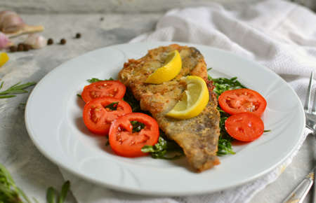 Fried fish fillet with tomatoes, lemon and rosemary. White plate. Light background. White linen napkin. Banco de Imagens
