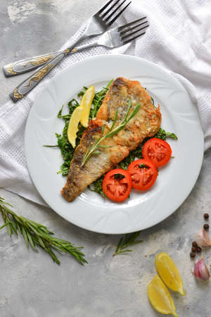 Fried fish fillet with tomatoes, lemon and rosemary. White plate. Light background. White linen napkin. Top view. Vertical view