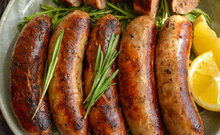 Grilled sausages with lemon and ketchup. Bavarian sausages with herbs and rosemary. Gray dark background. Gray plate and linen napkin. Closeup