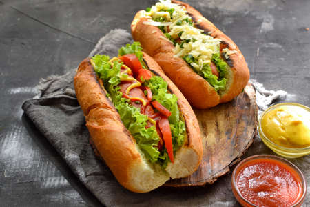 Hot dogs with various fillings. Dark background. food background with copy space. Hot dogs with mustard and ketchup, lettuce, cheese and tomatoes. Banco de Imagens