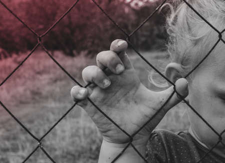 The child holds an iron fence with his hand. Sad child. Cruelty to children. Archivio Fotografico