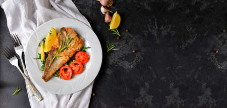 Fried fish fillet with tomatoes, lemon and rosemary. White plate. Dark background. White linen napkin. Top view. Free space for text