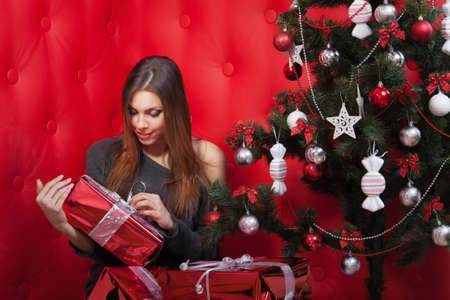 girl near the Christmas tree with gifts on red background photo