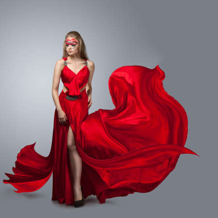 blonde in windy red  dress. Beautiful girl with creative make-up Stock Photo