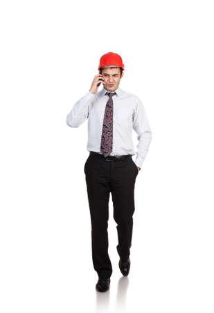 casco rojo: Hombre ingeniero en un casco rojo hablando por tel�fono Foto de archivo