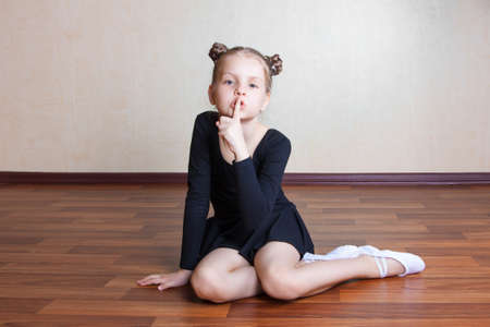 little blonde girl: little girl gymnast sitting on the floor