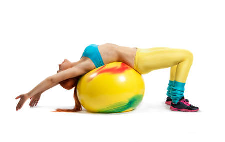 Young beautiful woman during fitness time and exercising with yellow  ball, isolated on white background photo
