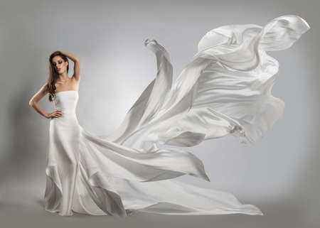 白いドレスを飛んで美しい若い女の子です。流れの布
