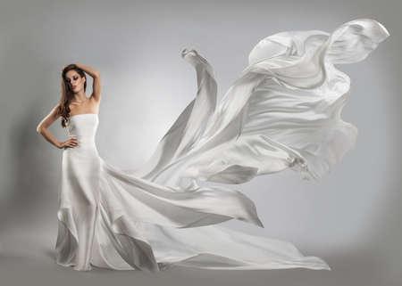 viento: hermosa joven en el vuelo de vestido blanco. Tela que fluye