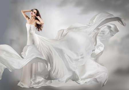 mooi jong meisje in vliegende witte jurk. Vloeiende stof