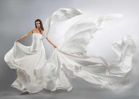 흰 드레스를 비행에서 아름 다운 젊은 여자. 흐르는 직물 스톡 콘텐츠