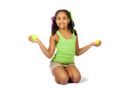 Girl with tennis balls sitting on the floor photo