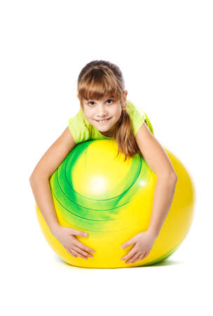 girl with yellow ball doing exercises on a white background photo