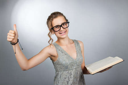 girl sit: Teen girl with book shows gesture class Stock Photo