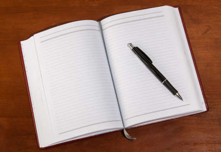 open diary: notebook on a wooden table. open diary and pen to record