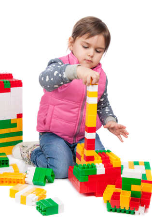 builds: little girl builds a tower isolation on white