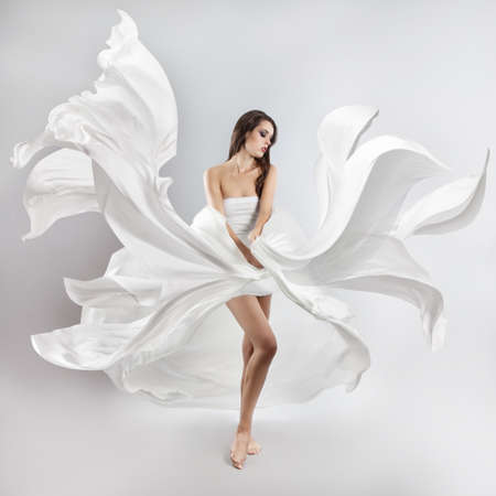 happy people white background: beautiful young girl in flying white dress. Flowing fabric