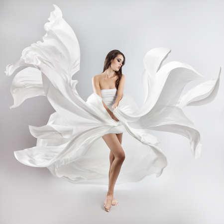 Hermosa joven en el vuelo de vestido blanco. Tela que fluye Foto de archivo - 47258293