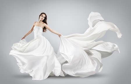 flowing: beautiful young girl in flying white dress. Flowing fabric