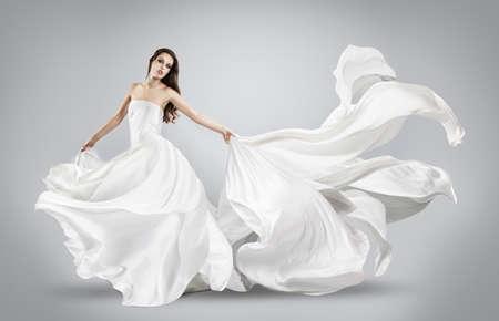 flujo: hermosa joven en el vuelo de vestido blanco. Tela que fluye