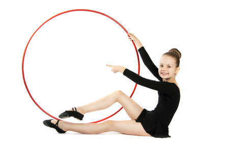 nine years old: nine years old gymnast with a hoop isolated on a white background. Girl sitting on the floor with a gymnastic hoop