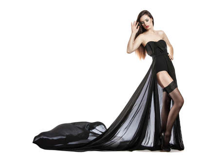 Girl in black dress billowing out flying transparent fabric. Model on a white background holding a flying dress