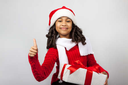 a child with a New Year gift. Joyful girl in a cap of Santa Claus. Girl showing thumbs