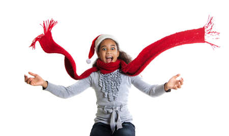 scarf: cheerful dark-skinned girl in a red scarf and hat of Santa Claus. Winter portrait of joyful adolescent girls Stock Photo