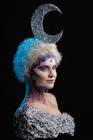 silver hair: Winter portrait of a girl with creative make-up on a dark blue background. Silvery Moon of silver hair in curls. Purple - Gold Makeup. Stock Photo