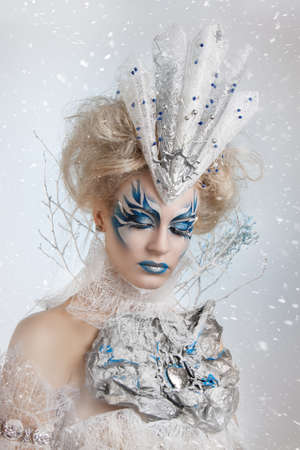Beautiful girl with creative make-up for the new year. Winter portrait. Bright colors, blue lips, elegant dress design hair. Conceptual art Фото со стока