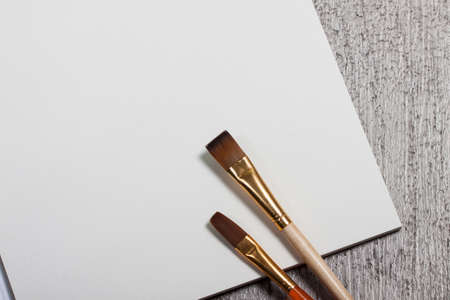 watercolor paper: Group of watercolor brush and blank white paper card on wood table ,Copy space for adding your content.