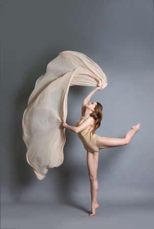 beautiful young girl dancing with brightly colored fabrics. Flying fluttering fabric. Girl throws a light fabric