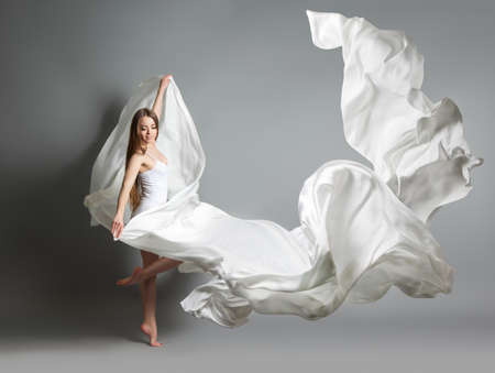 beautiful young girl dancing. The girl in flying white dress. A white cloth is flying in the air. White light dress Reklamní fotografie