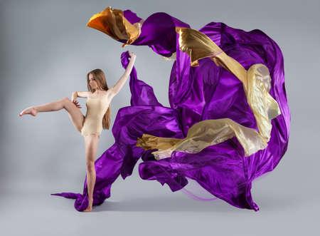beautiful young girl dancing. Flowing fabric. Girl throws up the fabric. Fabric flies Reklamní fotografie