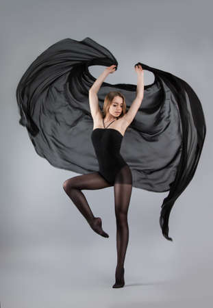 beautiful young girl dancing. Girl in black with a black cloth flying. Flowing fabric. Girl throws up the fabric. Fabric flies