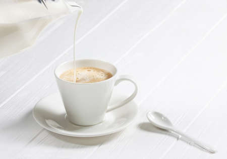 cup of hot cappuccino coffee on a white wood table. Milk being poured into a cup of coffee. Adding milk. Stock Photo