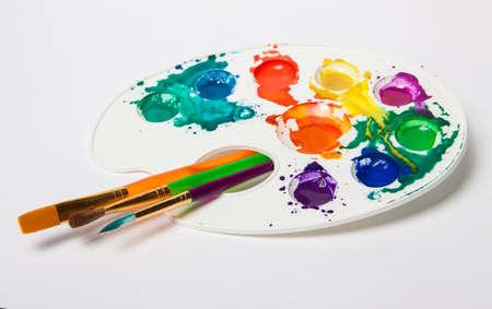 pallette: différents pinceaux de taille et la palette de couleurs. Peintures barbouillé sur une palette. fond clair avec pinceaux et de peinture