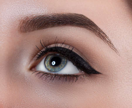 Female eye close-up. Macro. Perfect makeup and eyebrows. Beautiful gray eyes Stock Photo