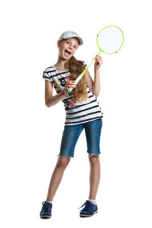 Pretty teen girl plays with a racket for a badminton on a white background. Girl in a cap, denim shorts and sneakers
