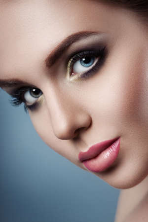 gentle dream vacation: The girls face close up. Beauty stock photos. Perfect skin, beautiful professional makeup. gray background