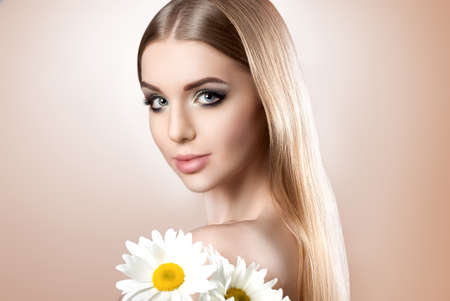 gentle dream vacation: Portrait of a young attractive girl with a beautiful make-up and perfect hair on a beige background. A girl holding a bouquet of daisies. Beautiful make-up, perfect skin and hair.