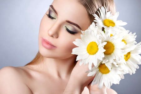 stock photos: Portrait of a young attractive girl with a beautiful make-up and daisies. Close-up, long hair, perfect skin. Stock photos on a light gray background Stock Photo