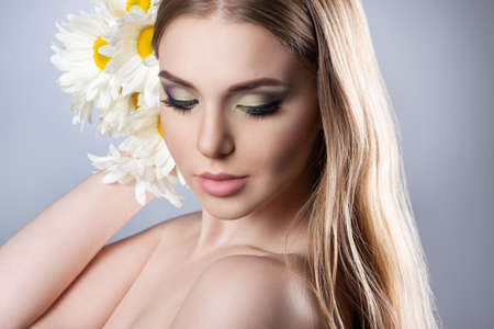gentle dream vacation: Portrait of a young attractive girl with a beautiful make-up and daisies. Close-up, long hair, perfect skin. Stock photos on a light gray background Stock Photo