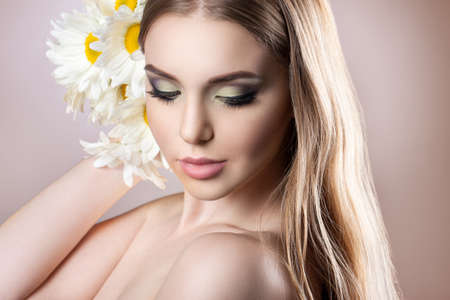 stock photos: Portrait of a young attractive girl with a beautiful make-up and daisies on the beige background. A girl holding a bouquet of daisies. near the hair. Stock photos on a beige background Stock Photo