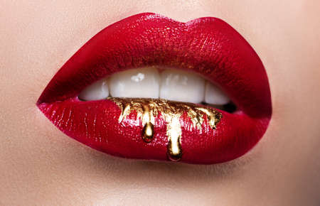 Beautiful female lips closeup. Red lipstick, gold paint flowing over his lips. Stock Photo Cosmetic Advertising Фото со стока