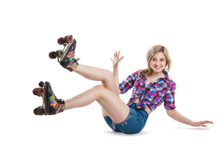 roller: Cheerful young girl in roller skates. A girl sits on the floor and laughs. It shows the gesture class. A fall. Stock Photo