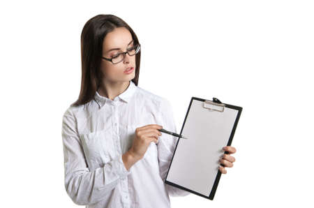 summarize: Young beautiful woman with a clipboard in his hands. Long-haired brunette in glasses and a white shirt. The woman points to the clipboard. Stock Photo